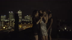 Female Friends party on rooftop at night taking selfie Stock Footage
