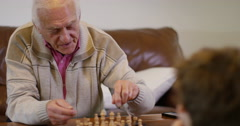 4K Family generations - Senior man playing chess at home with his grandson - stock footage