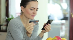 Smiling woman online shopping using mobile phone and credit card in kitchen HD - stock footage