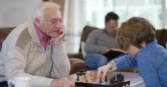 4K Family generations - father watches son playing chess with grandfather Stock Footage