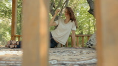 Young woman lying on a carpet in the gazebo in the woods Stock Footage