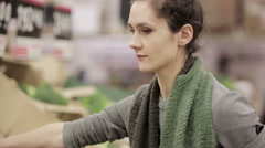 Young woman chooses cabbage on store shelves Stock Footage