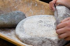 Making flour in a traditional way for the Neolithic era Stock Photos