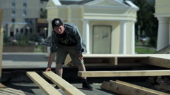 Man moves pieces of wood on the outdoor Stock Footage
