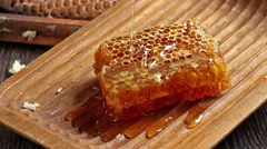 Honeycombs with pouring honey from wooden honey dipper - stock footage