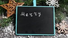 Writing Christmas greetings on black chalkboard Stock Footage