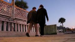 View from ground of boardwalk, couple walking by Stock Footage