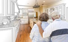 Senior Couple Looking Over Custom Kitchen Design Drawing and Photo Combinatio Stock Photos