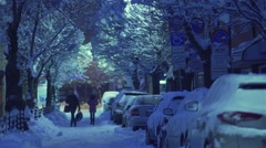 Mother with child walk on a snowy street in the early morning Stock Footage