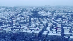 winter scene with snowy roofs and night lights from high above the city - stock footage