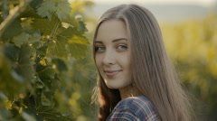 Attractive girl in a plaid shirt posing next to the vine Stock Footage