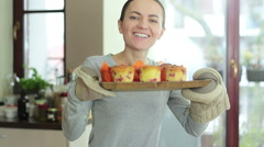 Portrait of young smiling woman holding a tray with cupcakes at the kitchen HD Stock Footage