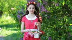 Beautiful woman in a red dress with a wreath and a basket with tulips Stock Footage