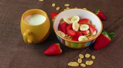 Healthy breakfast. Cornflakes, fresh strawberries, banana and milk Stock Footage