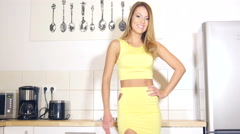 Attractive girl in dress in kitchen smiling before work Stock Footage