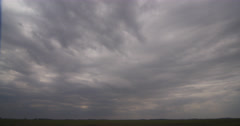 Clouds advancing toward the camera over green prairie Stock Footage
