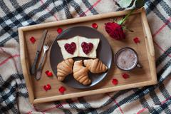 Valentines day breakfast in bed with rose flower and petals Stock Photos