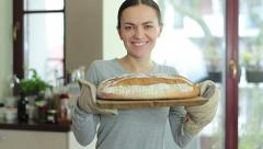 A young smiling woman standing in her kitchen holding freshly baked bread  HD Stock Footage