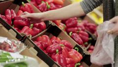 Young woman chooses paprika on store shelves Stock Footage