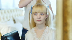Blonde young bride doing her hair - stock footage