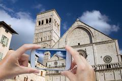 Taking pictures by smart phone in Assisi (Italy) - stock photo