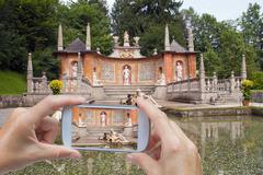 Taking pictures by smart phone in Hellbrunn Stock Photos