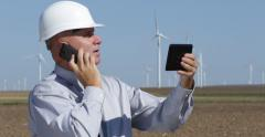 Energy Industry Engineer Check Wind Farm Report Use Touch Tablet Mobile Phone Stock Footage