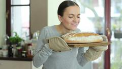 Young woman smelling freshly baked bread in kitchen HD Stock Footage