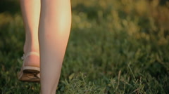 Lovely girl dressed in a shirt and shorts walking on green grass - stock footage