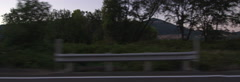 Left Side view of a Driving Plate: Car travels at dusk past farms and vineyards Stock Footage