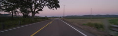 Front view of a Driving Plate: Car travels at dusk past farms and vineyards on Stock Footage