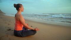 Woman meditating at beach Stock Footage