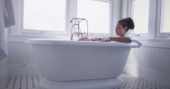 Beautiful young mixed race woman taking a bath Stock Footage