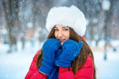 A girl in a white fur hat covers her face with her hands dressed in blue mittens - stock photo
