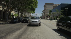 Rear view of a Driving Plate: Car travels on Colorado Boulevard through downtown Stock Footage