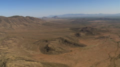 Slow flight past barren desert landscape with low mountains in background Stock Footage