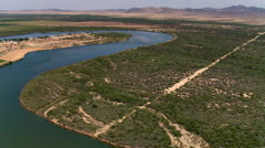 Flying above a bend of the Colorado River near agricultural land - stock footage