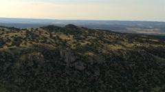 Flight over a hilly landscape freckled with arid-land vegetation - stock footage