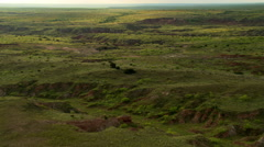 Flight over a green prairie cut by a meandering muddy stream - stock footage