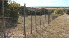 Wire fence on hill slope with long view of valley in background Stock Footage