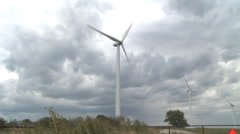 Wind turbines turning against a cloudy sky - stock footage