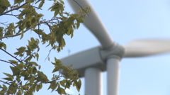 Rack focus leafy branches and a close-up wind turbine's rotors - stock footage
