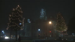 Lighted Christmas trees and evening traffic in front of a 19th Century civic - stock footage