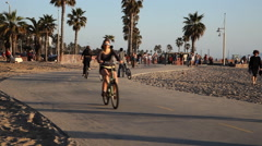 Pedestrians and cyclists on a bike path at Venice Beach, California Stock Footage