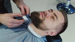 Corrects the shape of a beard at the hairdresser Stock Footage