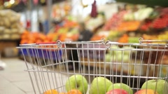 Shopping cart with vegetables on the background of the market - stock footage