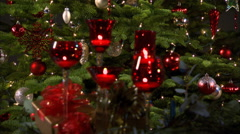 Rack-focus twinkling tea lights in red stemmed glasses in front of a Christmas Stock Footage