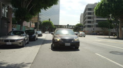 Rear view of a Driving Plate: Car turns right from East Olympic Boulevard in Los Stock Footage