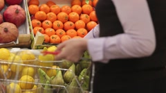 Woman with a shopping cart makes shopping at fruit store Stock Footage