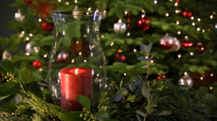 A red candle in a glass lantern chimney in front of a Christmas tree Stock Footage